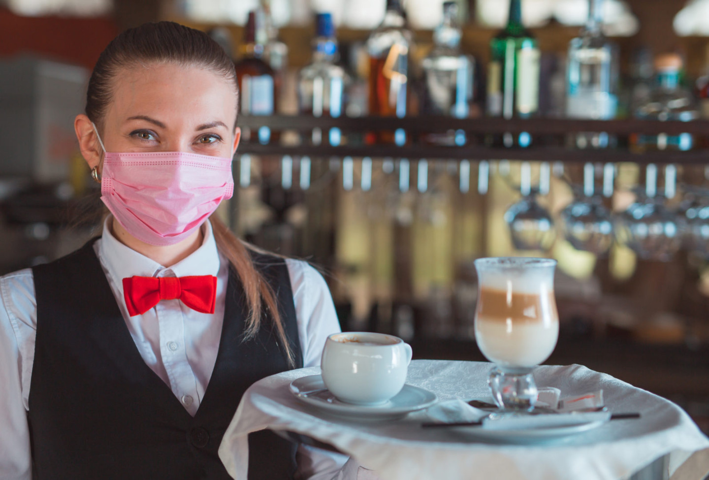 the waiter works in a restaurant in a medical mask.