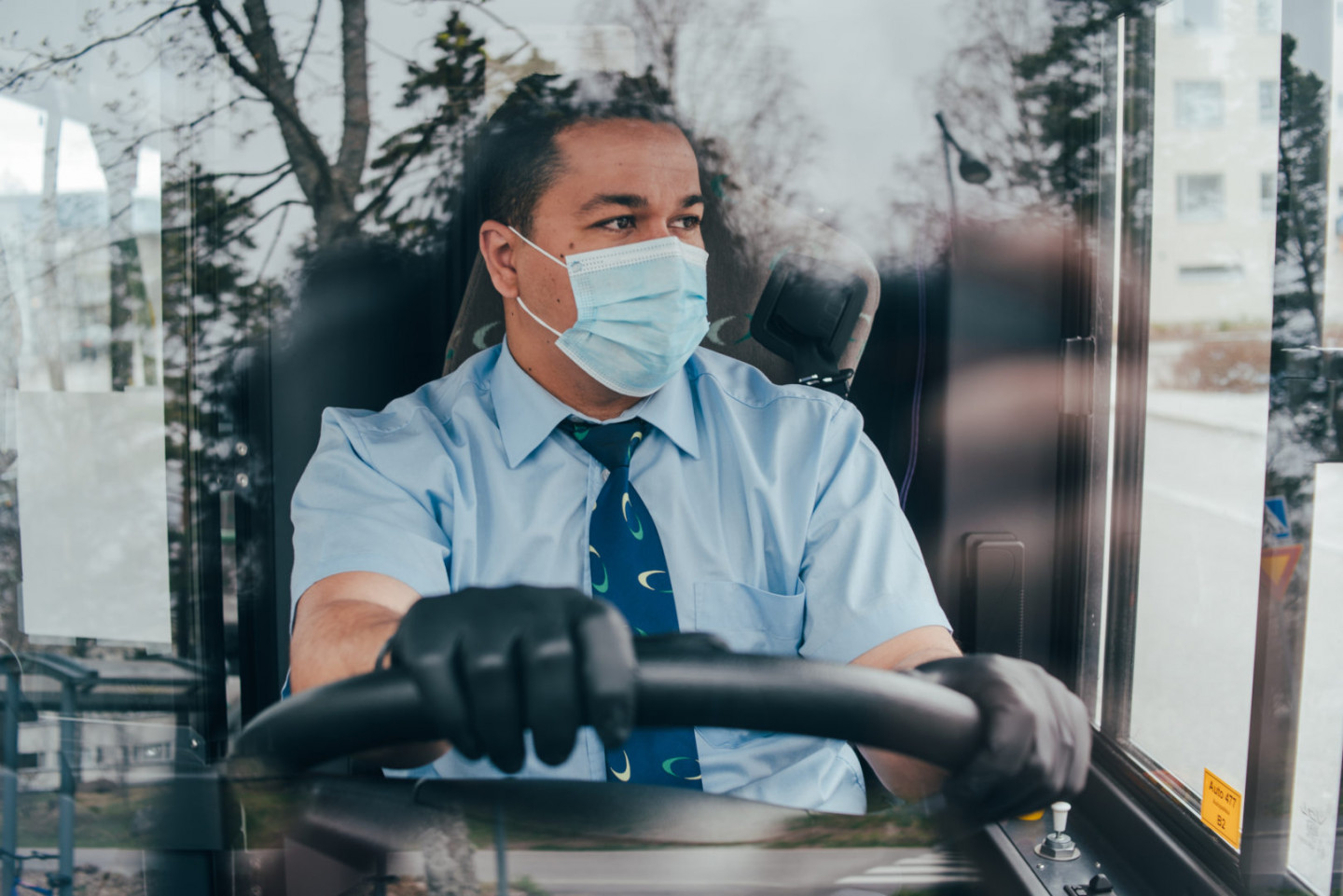 prevent the spread of coronavirus. young hispanic bus driver wearing a protective mask and looks at road.