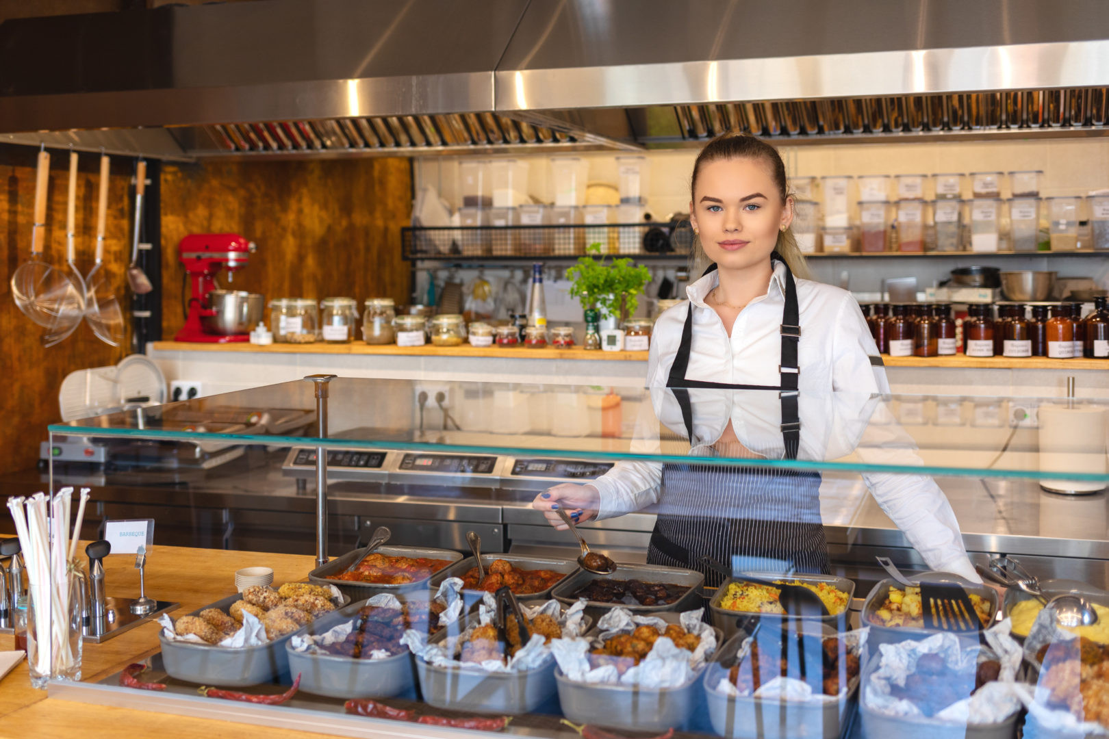 New business owner or woman waitress working behind counter in small restaurant serving food